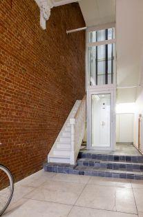 De witte, moderne structuur van de lift vormt een mooi contrast met de omgeving